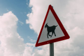 Fotografie triangle goat warning sign against sky with clouds