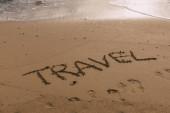 Fotografie pláž s cestovním nápisem na písku u moře