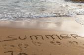 Fotografie pláž s letním nápisem na písku u moře