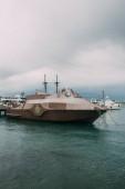 retro loď v blízkosti jachty ve středozemním moři proti obloze s mraky