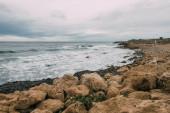 nyugodt tengerpart kövekkel közel a kék tengerhez