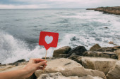 Fotografie Frau hält wie am Stock in der Nähe von Felsen und Meer