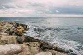 Photo tranquil coastline with rocks near mediterranean sea against cloudy sky