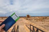 ostříhaný pohled na muže držícího pas a palubní lístek poblíž starobylého domu Theseus
