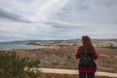 zpět pohled na cestovatele s batohem v blízkosti rostlin a Středozemního moře