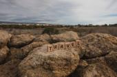 dřevěné kostky s cestovním nápisem na skále proti obloze