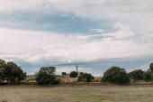 zelené stromy a bílý maják proti modré obloze s mraky