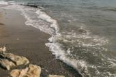 mokrý písek a skály v blízkosti Středozemního moře