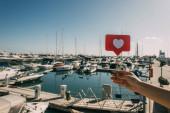 Ausgeschnittene Ansicht einer Frau, die ein rotes Herz am Stock hält, als wäre sie in der Nähe von angedockten Schiffen im Mittelmeer