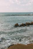 sziklák a Földközi-tengeren a kék ég ellen a felhőkkel