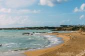 Fotografie pobřeží a písečná pláž v blízkosti středozemního moře proti modré obloze