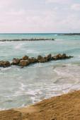 mokré kameny v modré středozemní moře proti obloze s mraky