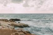pobřeží s kameny v blízkosti Středozemního moře proti obloze s mraky