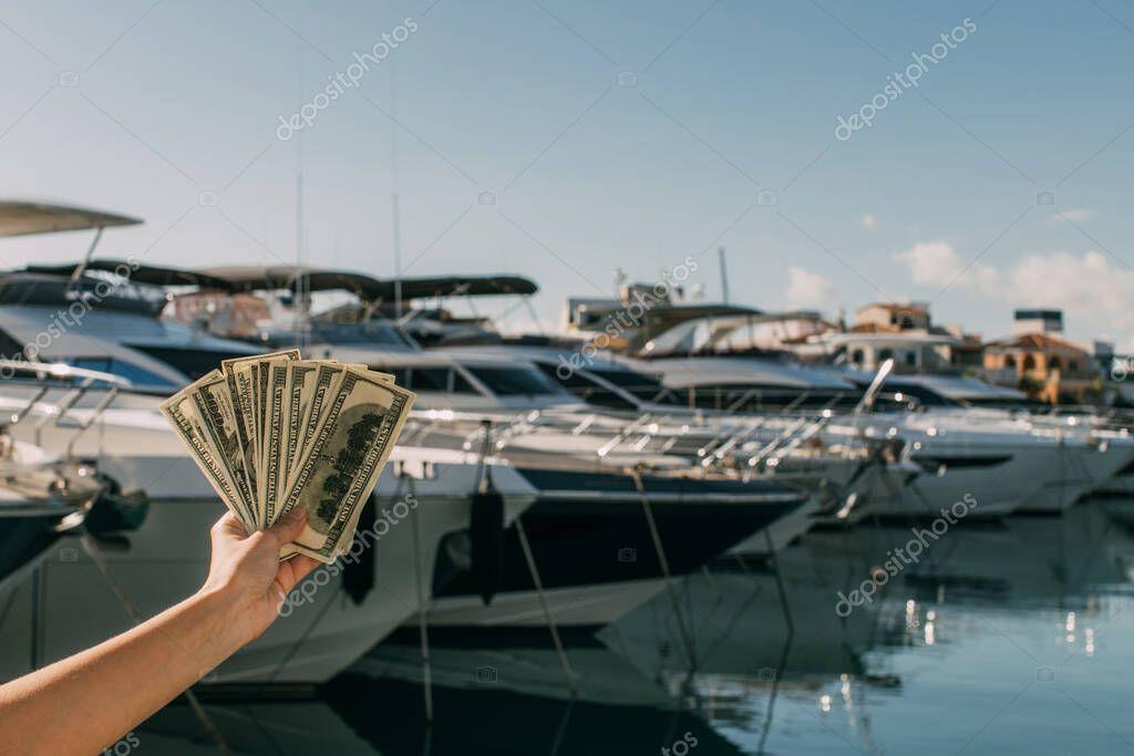vista ritagliata di donna che detiene banconote in dollari vicino agli yacht nel Mar Mediterraneo
