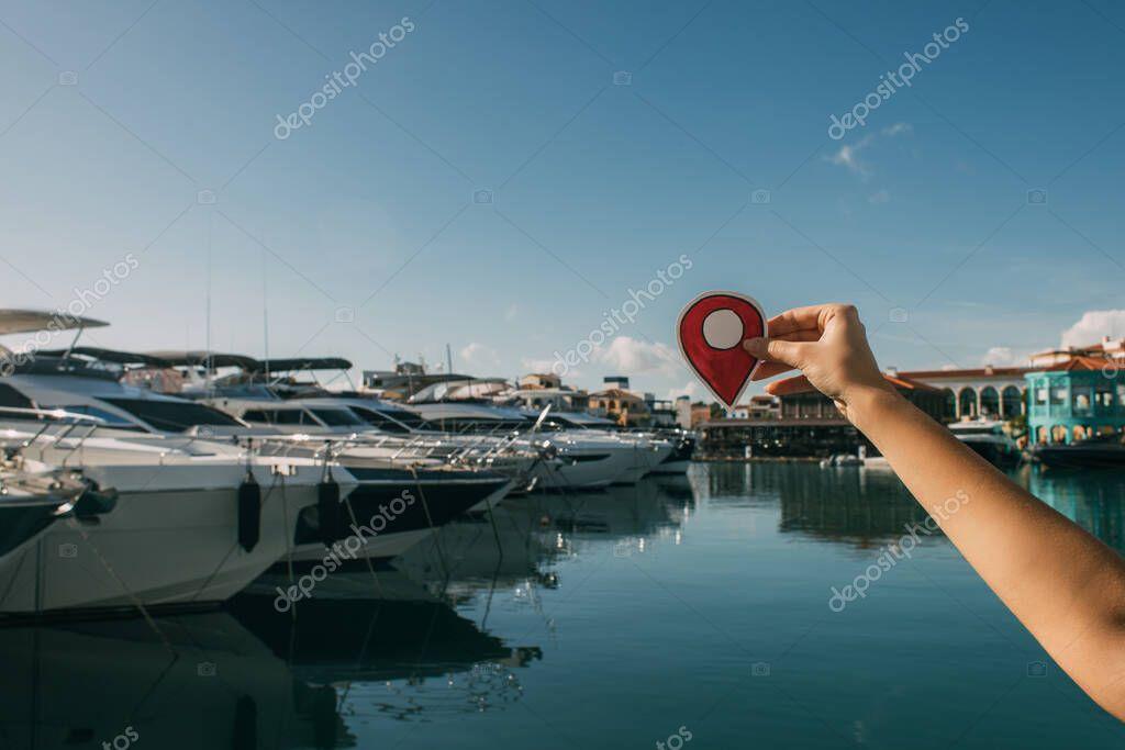 vista ritagliata di donna in possesso di carta rossa con cartello di posizione vicino alle navi attraccate nel Mar Mediterraneo