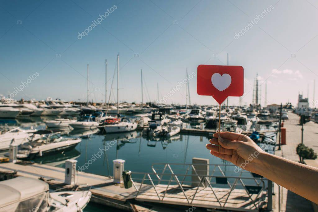 vista ritagliata della donna che tiene il cuore rosso sul bastone come vicino alle navi attraccate nel Mar Mediterraneo