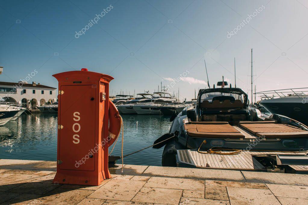 cabina rossa con scritte sos vicino agli yacht nel Mar Mediterraneo