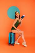 Dívka s pasem a letenkou se usmívá, dívá se do kamery a sedí na kufru s modrým kruhem vzadu na oranžové