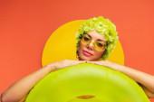 Porträt eines Mädchens mit Hut, dekorativen Blumen und Sonnenbrille, die Hände auf Schwimmring in gelb und orange legen