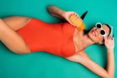 Draufsicht einer lächelnden Frau, die eine Flasche Sonnencreme auf Türkis hält