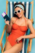 Magas látószögű kilátás nő mosolyog, és bemutatja útlevél repülőjegy fedélzeti szék a kék