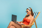 Freelancer with crossed legs smiling and working with laptop on deckchair isolated on blue