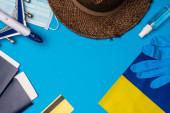 Horní pohled na vlajku Ukrajiny, kreditní karta v blízkosti hračky letadlo a sprej láhev ruční dezinfekci na modrém pozadí