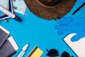 Draufsicht auf Spielzeugflugzeug in der Nähe medizinischer Maske, Sonnenhut mit Pässen und Latex-Handschuh auf blauem Hintergrund