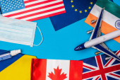 Photo Top view of toy plane near medical mask and flags of countries on blue background