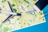 Top kilátás játék repülőgép közelében beszéd buborék, ahol a maszk felirat közelében útlevél és üveg kézfertőtlenítő a térképen a kék felületen