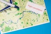 Fotografie Horní pohled na kartu se zrušením letu s letadlem hračky na mapě izolované na modré