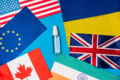 Top view of bottle of hand sanitizer near flags of countries on blue background