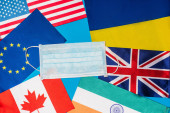Top view of medical mask on flags of countries isolated on blue