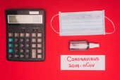 Top view of medical mask, hand sanitizer with calculator and lettering coronavirus 2019-nCov on card on red surface