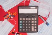 Horní pohled na kalkulačku v blízkosti pilulky, lékařské masky a zkumavky s krevním vzorkem a koronavirem nápisy na červeném pozadí