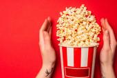 Draufsicht auf weibliche Hände in der Nähe von Eimer mit leckerem Popcorn auf rotem Hintergrund
