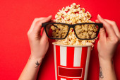 Draufsicht des Mädchens mit Sonnenbrille in der Nähe von Pappeimer mit Popcorn auf rotem Hintergrund