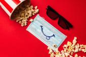 Top kilátás napszemüveg, vödör popcorn és orvosi maszk mosollyal piros háttér