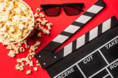 Draufsicht auf Klappbrett neben Eimer mit Popcorn und Sonnenbrille auf rotem Hintergrund