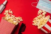 Top kilátás popcorn, orvosi maszk kézfertőtlenítővel és napszemüveg piros háttér