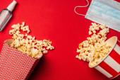 Draufsicht auf Händedesinfektionsmittel, medizinische Maske und Eimer mit Popcorn auf roter Oberfläche