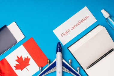 Top view of toy plane, card with flight cancellation lettering and flag of canada on blue background stock vector