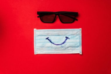 Top view of medical mask with smile and sunglasses on red background stock vector