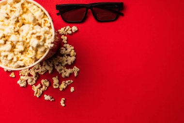 Top view of sunglasses near bucket with tasty popcorn on red background stock vector