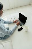 Fotografie Hochwinkelaufnahme eines afrikanisch-amerikanischen Freelancers mit Laptop mit leerem Bildschirm in der Nähe von Smartphone und leerem Becher