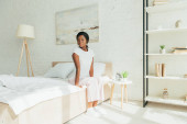 Photo beautiful african american girl in pajamas sitting on bed and looking away in morning