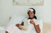 boldog afro-amerikai lány álommaszkkal a homlokán ül az ágyban, könyv és egy csésze kávé a kezében