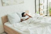 afro-amerikai lány álommaszkban alszik fehér ágynemű a tágas hálószobában