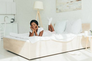 Happy african american girl smiling at camera while lying on white bedding stock vector