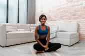 Africká americká sportovkyně se usmívá, dívá se do kamery a sedí v lotosu pózovat na podložce jógy v obývacím pokoji